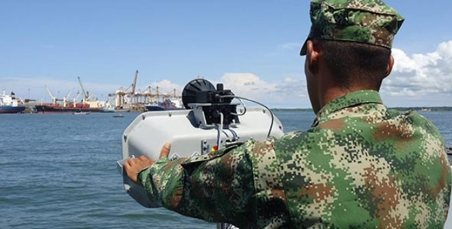 Image of a soldier using an LRAD device at a shipyard